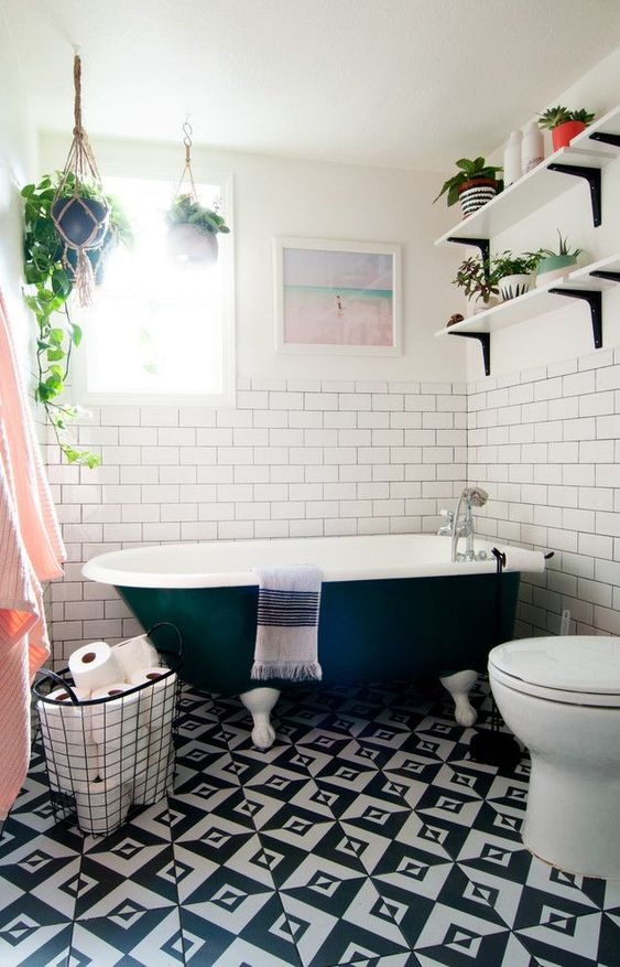 an eclectic bathroom with potted greenery, black and white tiles on the floor and touches of blush