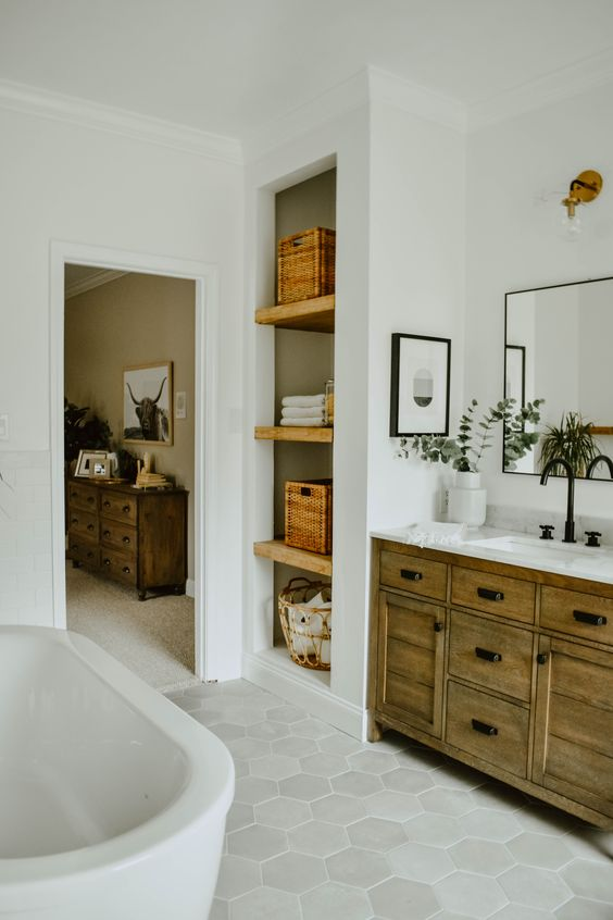 an eclectic boho meets mid-century modern bathroom with a wooden vanity, baskets, hex tiles and potted greenery