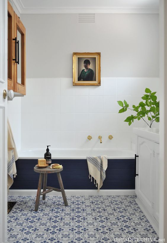 an eclectic space done in navy and white, with grey touches and natural wood plus potted greenery