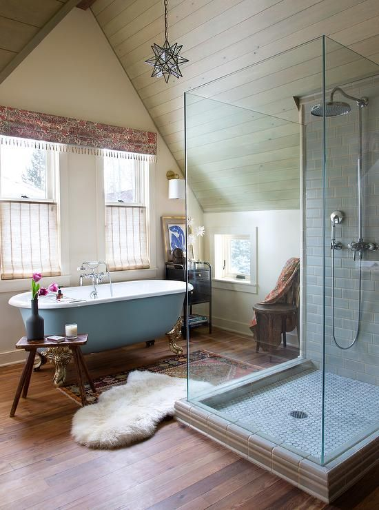 an opulent eclectic bathroom with touches of powder blue, a tiled shower, boho rugs and a boho printed curtain