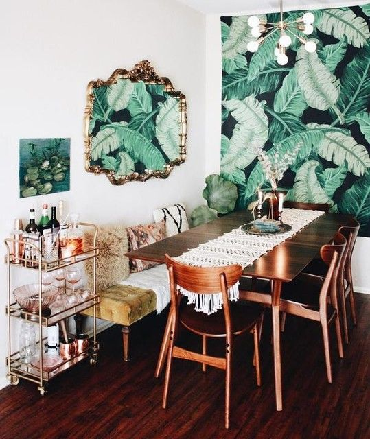 a dining room with a tropical leaf print wallpaper wall and a matching artwork on the next wall for an accent
