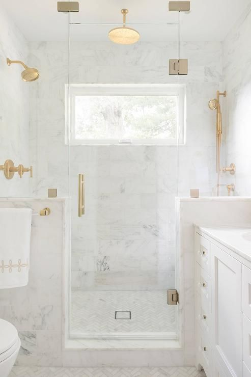 a white marble bathroom done with gold fixtures looks flawlessly elegant and very refined