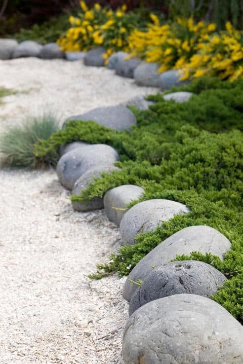 oversized rocks and white garden pathways create an Asian feeling in the garden makign it all-natural yet manicured