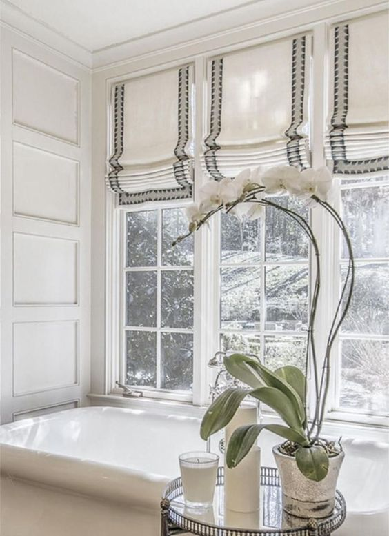 striped Roman shades are a chic idea for a modenr bathroom, they make it feel more welcoming and you can keep privacy any time