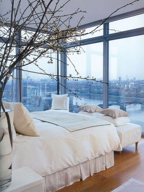 this bedroom with a view features totally no window treatments that allow enjoying the views anytime
