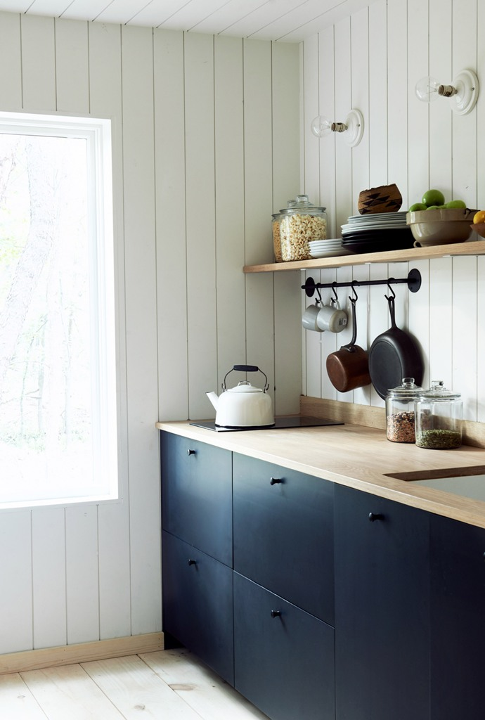 The kitchen is done with sleek navy cabinets, light-colored wooden shelves and countertops and there's much natural light