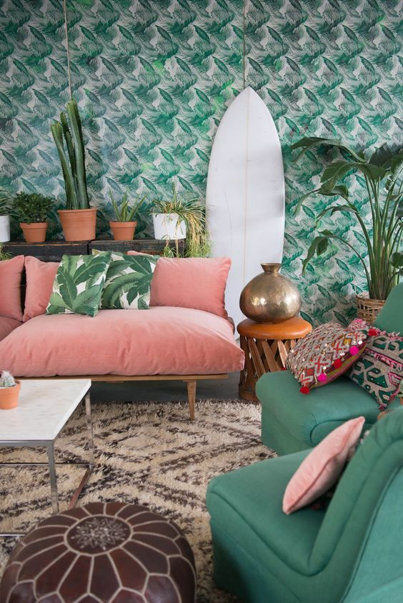 a bright living room with tropical leaf print wallpaper and matching pillows plus colorful furniture