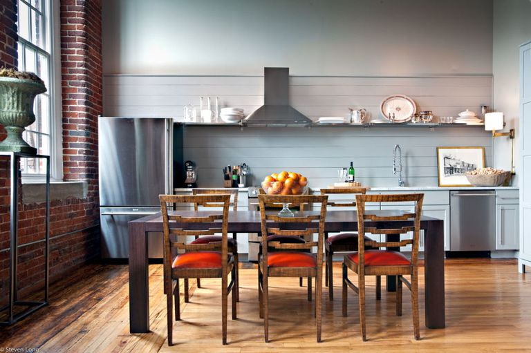 a chic kitchen done with grey shiplap that features a statement wall and a backsplash and orange chairs for a touch of color