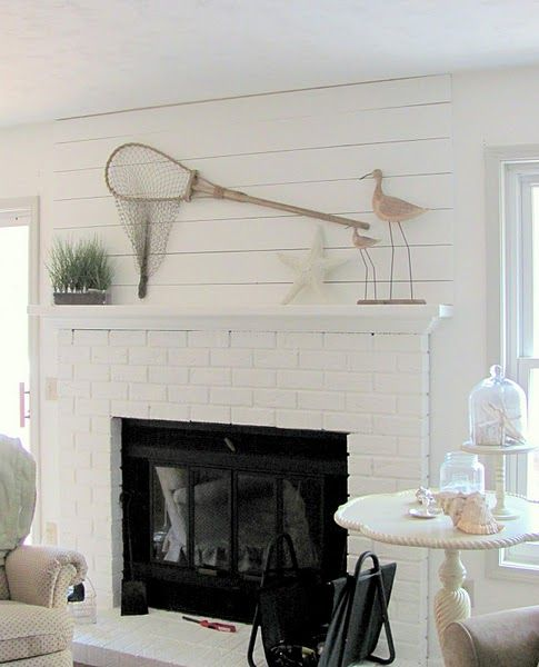 a coastal living room with a white brick clad fireplace - whte brick accents the fireplace and adds texture