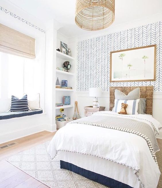 a kid's room accented with a statement wall with catchy printed wallpaper for a boho feel