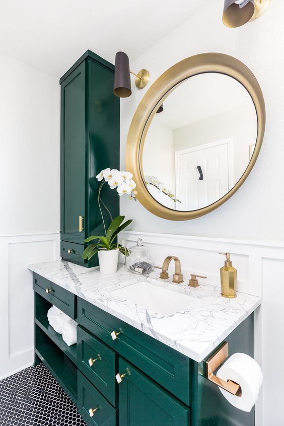 a stunning emerald and white stone bathroom spruced up with gold hardware and a large round mirror