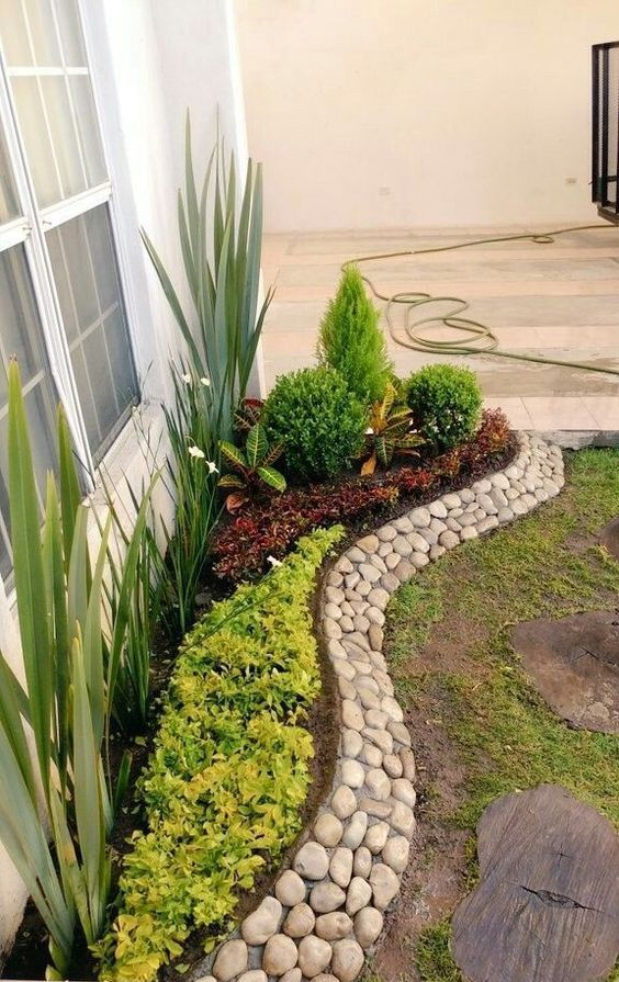 a stylish and creative pebble border is a cool way to add texture and interest to your raised garden bed
