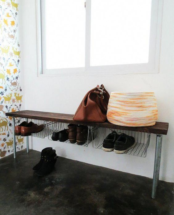 an industrial bench with metal legs, a wooden seat and wide shelves for storing shoes is a genius idea