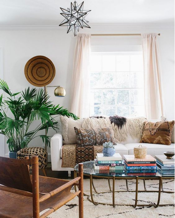 various printed and fringed pillows, a rug and a pritned upholstered ottoman for a boho living room