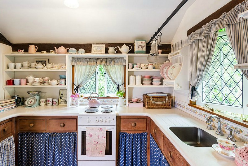 The kitchen is done with lots of built in shelves, rich stained cabinets with polka dot fabric covers and small windows