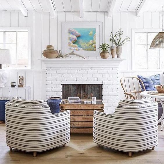 a coastal living room with a fireplace clad with white bricks that highlight this feature and add interest