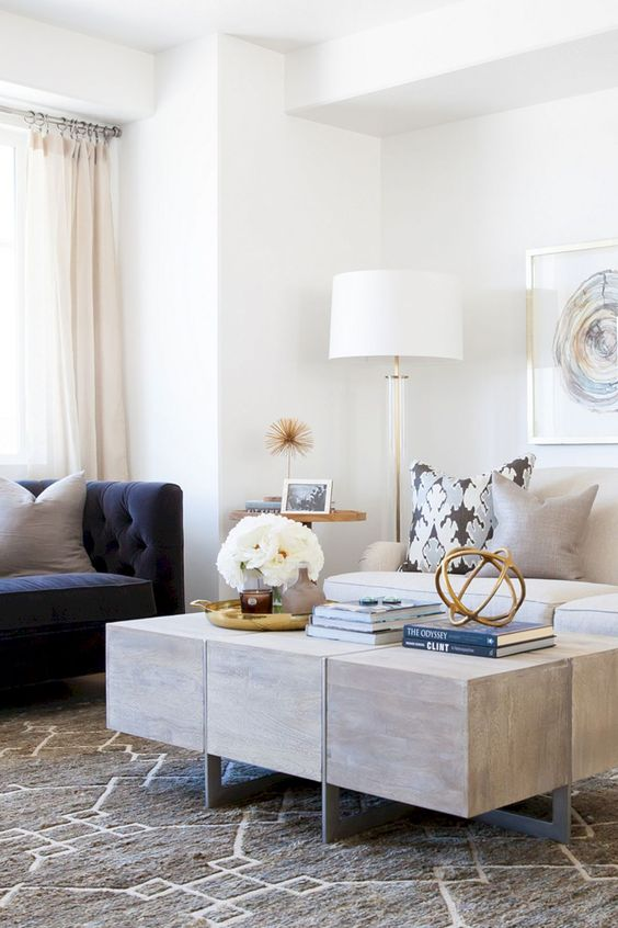 a contemporary living room with a white and navy sofa with a tall back plus a wooden coffee table