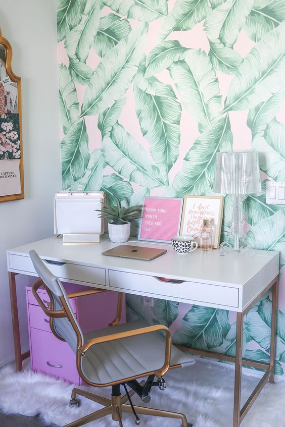 a girlish home office with banana leaf print wallpaper, touches of pink and brass