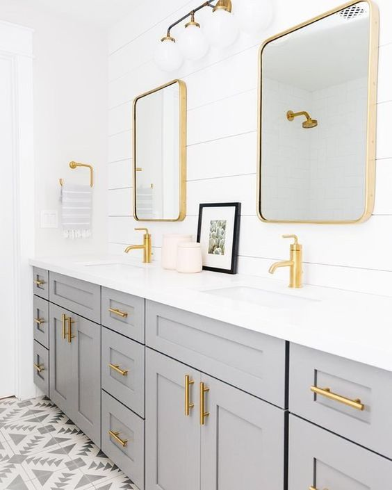 a grey double vanity, a white shiplap wall and gold fixtures, hardware and gold mirror frames