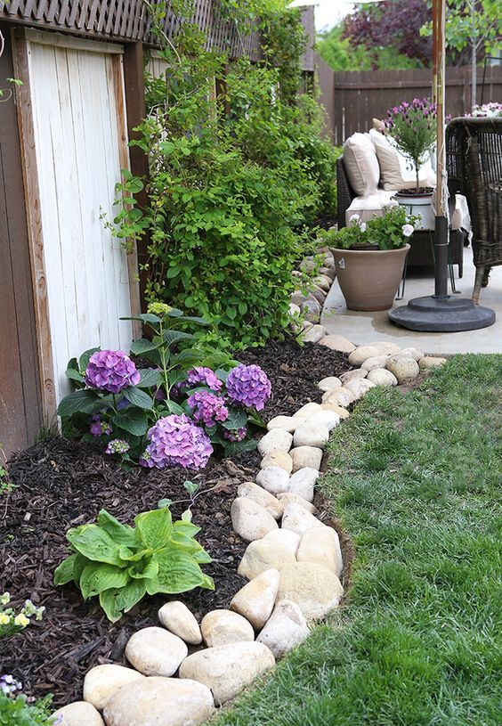 a river rock border brings a natural feel to the garden - the rocks show off different sizes and shapes