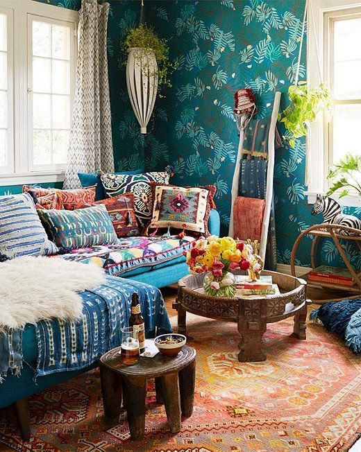 colorful and bright printed pillows and a blanket plus a rug and a faux fur piece make up the whole space
