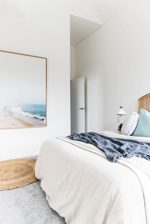 a neutral coastal bedroom done in white, off-white and light grey plus touches of aqua