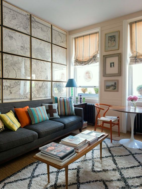 an eclectic living room  with a whole statement wall done with framed vintage maps all over