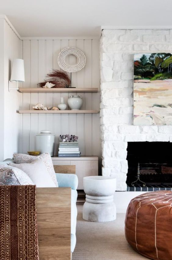 another white brick clad fireplace is the coziest and coolest decor feature in the coastal living room