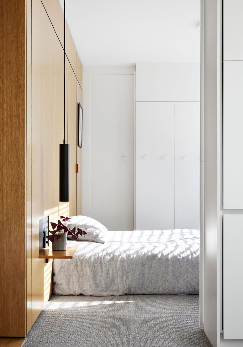 The bedroom is small and laconic, it features a woodne headboard that acts as storage, floating nightstandns and pendant lamps