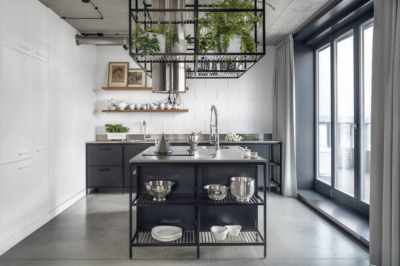 The kitchen is done with black metal cabinets and a kitchen island, with a subway tile wall and a cube with potted greenery