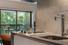 06 The kitchen is pretty small, there are white sleek cabinets, a neutral tile backsplash and additional lights