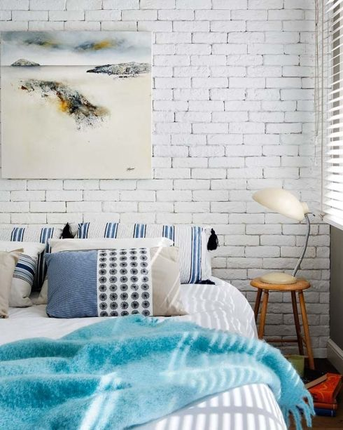 a beach inspired bedroom with a statement white brick wall that highlights the artwork and contrasts the colorful bedding