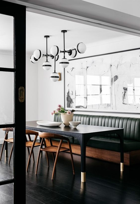 a black dining table, a green leather bench and stylish wooden chairs for a contemporary space