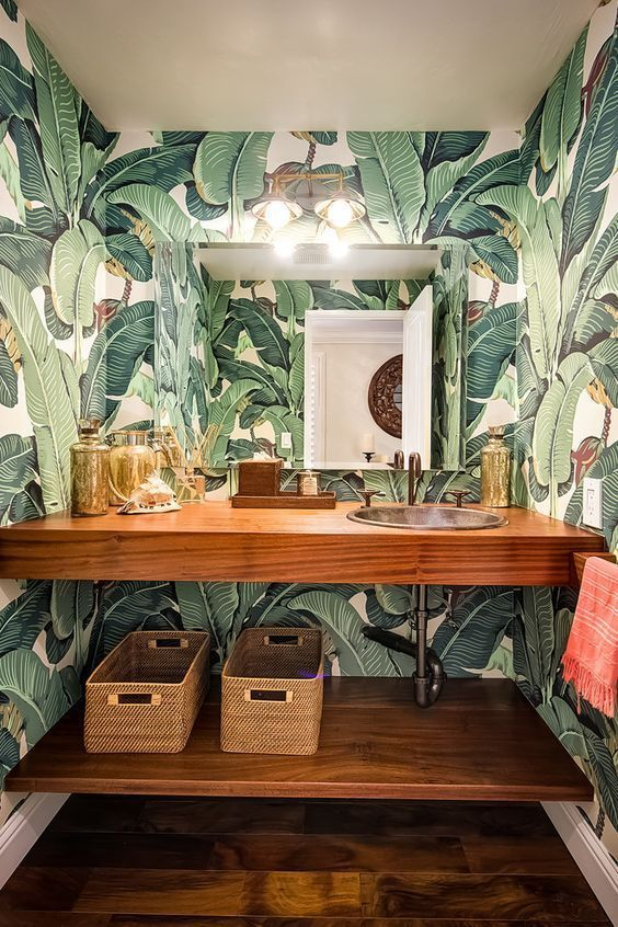 a chic powder room done with bright tropical print wallpaper and wooden items