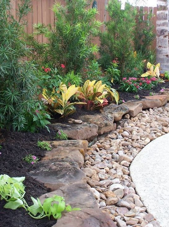 a large pebble and rough rock garden border brings much texture and a rough touch to the elegant outdoor space