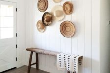 06 a simple entryway with a rough wooden bench and a white shiplap wall highlighted with decorative baskets and hats