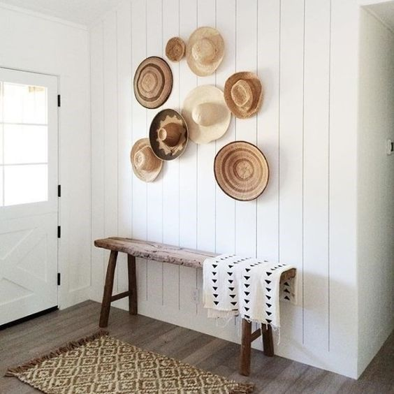 a simple entryway with a rough wooden bench and a white shiplap wall highlighted with decorative baskets and hats