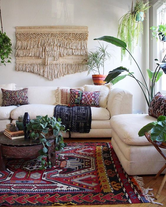 colorful printed pillows, a printed rug and a large macrame hanging make the space boho like
