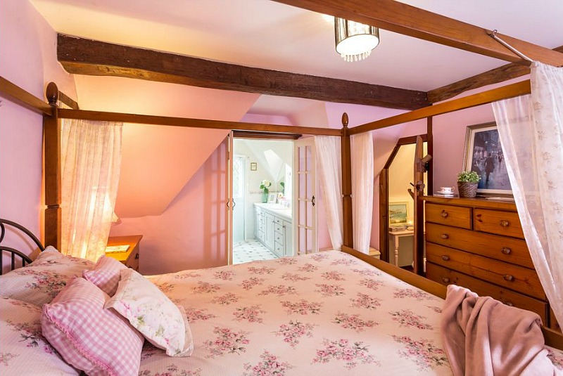 One bedroom is done in pink with a large canopy bed and a large wooden dresser