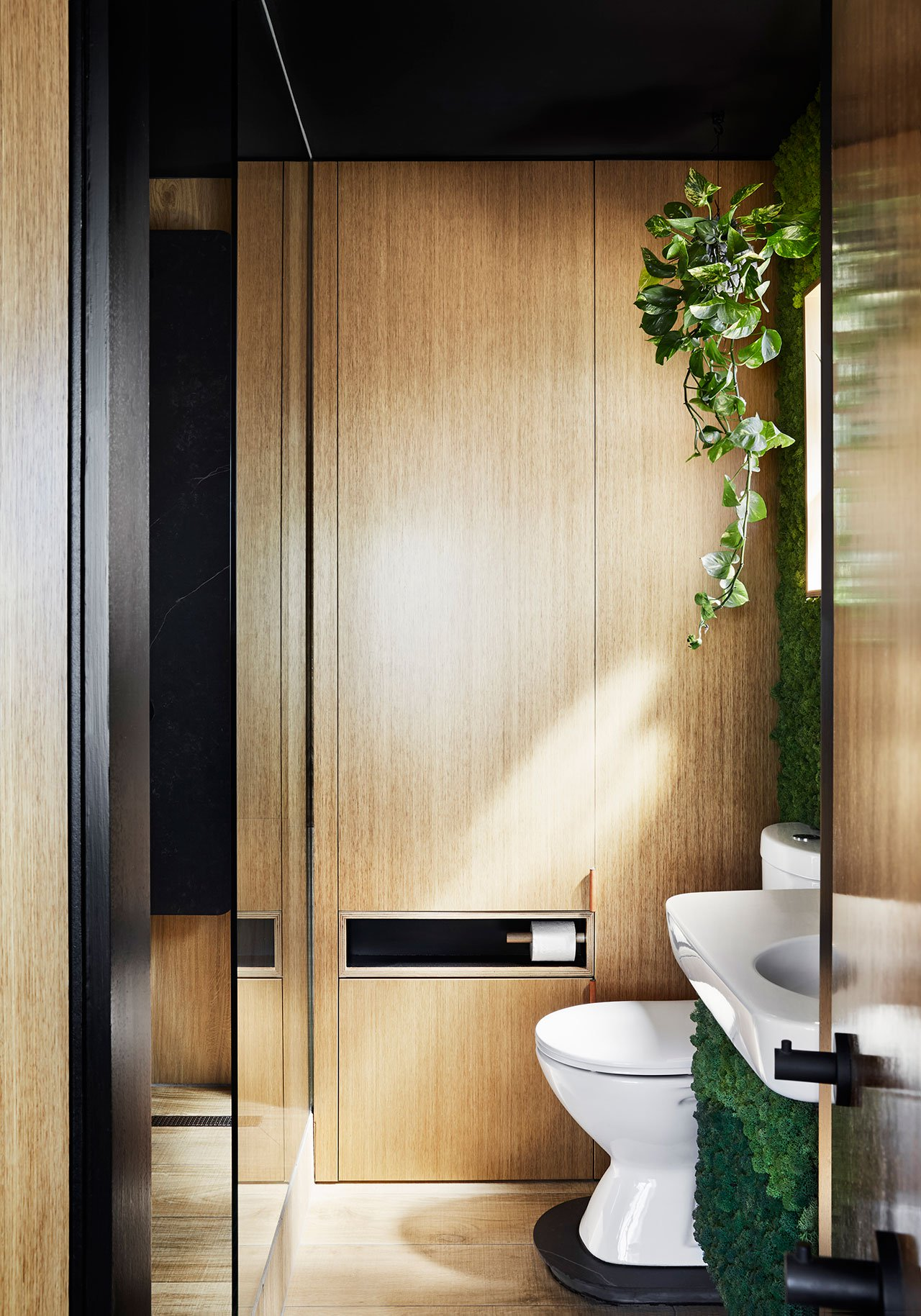 The bathroom features a shower and much light colored wood and black surfaces to continue the color scheme of the apartment