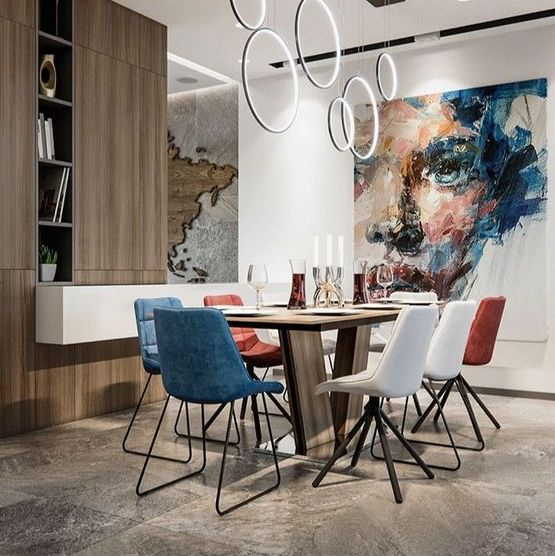 a contemporary dining room with white, red and blue mismatching chairs and a wooden table