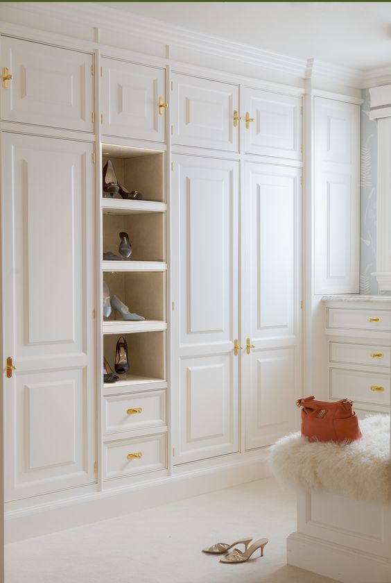 a neutral closet with gold hardware that adds chic and elegance to the space making it more welcoming
