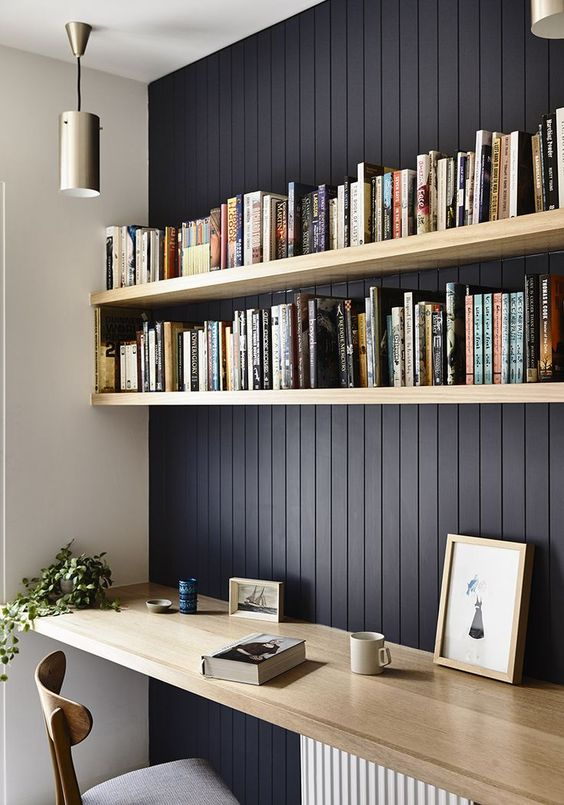 a stylish contemporary home office with black vertical shiplap on the statement wall and light stained wooden furiture