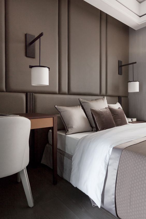 a taupe wall with upholstered panels over the bed substitutes the headboard and makes the space cozier