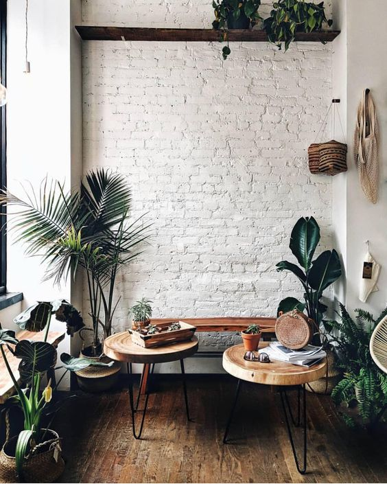 a white brick wall adds texture to this cozy boho chic nook and makes a nce backdrop for greenery and stained furniture