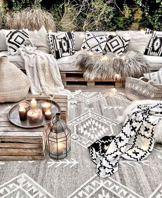 black and white pillows, a blanket and a matching rug in grey and white with tribal prints