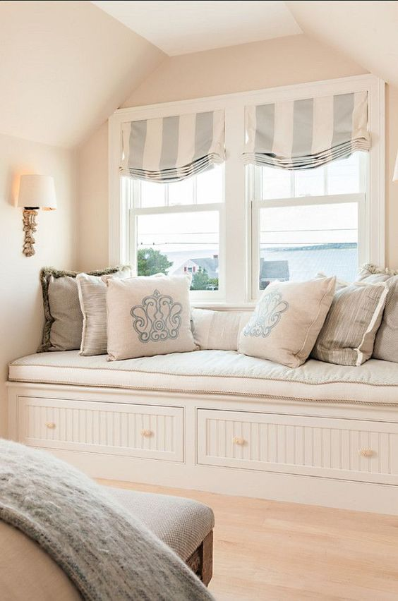 striped Roman shades in light blue and ivory add a vintage feel to the window nook and bring in a touch of subtle color