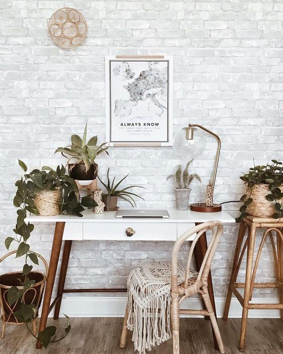 a boho chic home office nook with a whitewashed brick wall that creates a perfect backdrop and brings interest