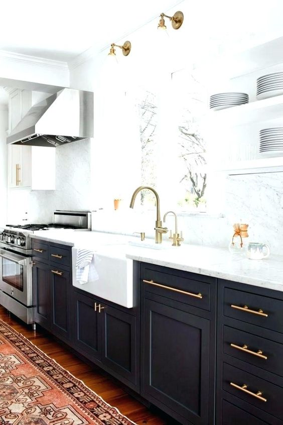 a chic black and white kitchen with gold hardware and matching lamps over the basin