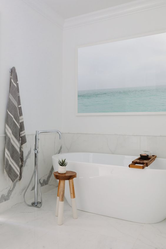 a fresh and airy bathroom done in white and creamy shades, with light greys and an aqua artwork showing the sea